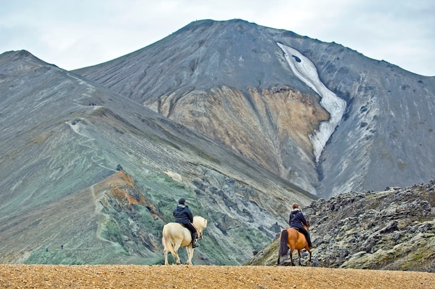 The rider rides on an icelandic horse against a mountain landscape