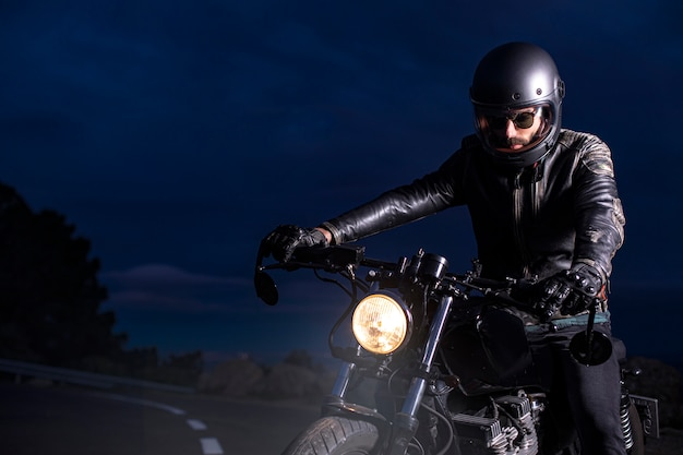 Rider with black cuscom motorcycle on the road at dusk