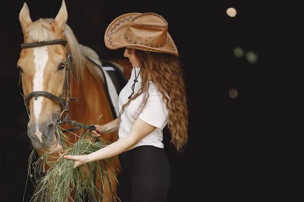 馬小屋で干し草を馬に与えるライダーの女性。女性は長い髪と白いtシャツを持っています。背景は暗くて黒です。