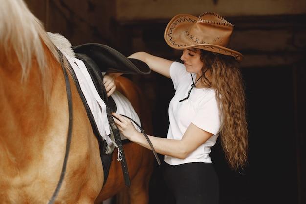 馬小屋でサドルを固定するライダーの女性。女性は長い髪と白いtシャツを持っています。背景は暗くて黒です。