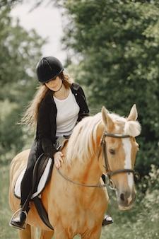 牧場で馬に乗るライダーの女性。女性は長い髪と黒い服を着ています。彼女の茶色の馬に触れる女性の乗馬。