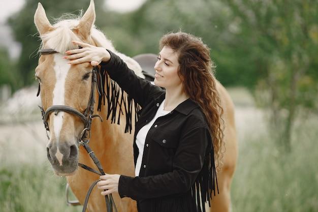牧場で彼女の馬と話しているライダーの女性。女性は長い髪と黒い服を着ています。馬の手綱に触れる女性の馬術。