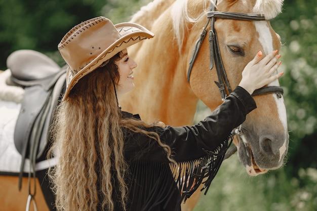 牧場で彼女の馬と話しているライダーの女性。女性は長い髪と黒い服を着ています。馬に触れる女性の乗馬。
