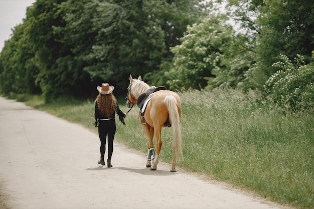 牧場で馬と一緒に歩くライダーの女性。女性は長い髪と黒い服を着ています。馬の手綱を握っている女性の乗馬。