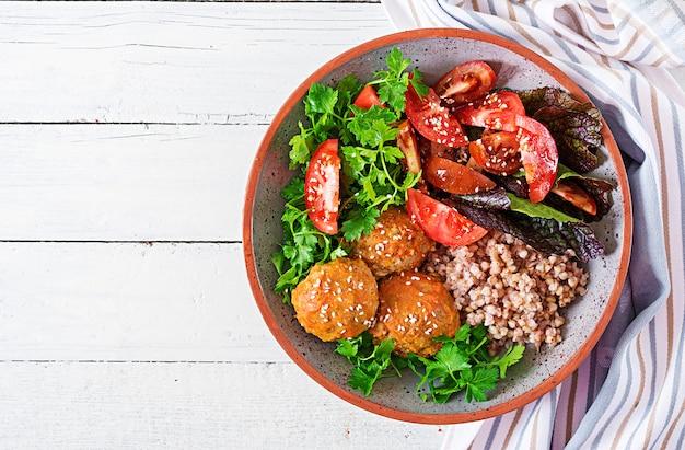 ミートボール、トマトのサラダ、白い木製のテーブルにソバのおridge。健康食品。ダイエット食事。仏bowl。上面図。平置き