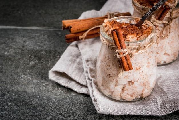 スペイン、南アメリカ、メキシコのデザート。甘いおridge、ライスプディング。アロズ・コン・レッシュ。シナモンと砂糖で飾られたポーションジャー。暗い石のテーブルの上。コピースペース