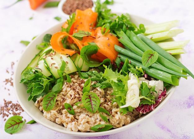 ダイエットメニュー。健康的な生活様式。エンバクのおridgeと新鮮な野菜とセロリ、ほうれん草、キュウリ、ニンジン、玉ねぎのプレート。