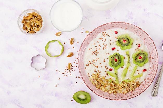 キウイ、ザクロ、ナッツ入りのおいしいヘルシーなオートミールのおridge。健康的な朝食。フィットネス食品。適切な栄養。上面図