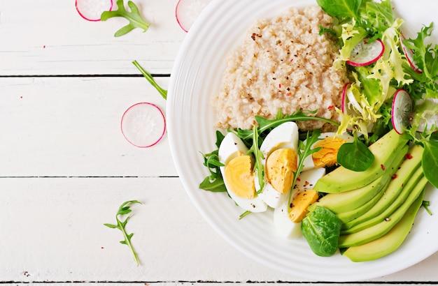 健康的な朝食。食事メニュー。オートミールのおridgeとアボカドのサラダと卵。上面図