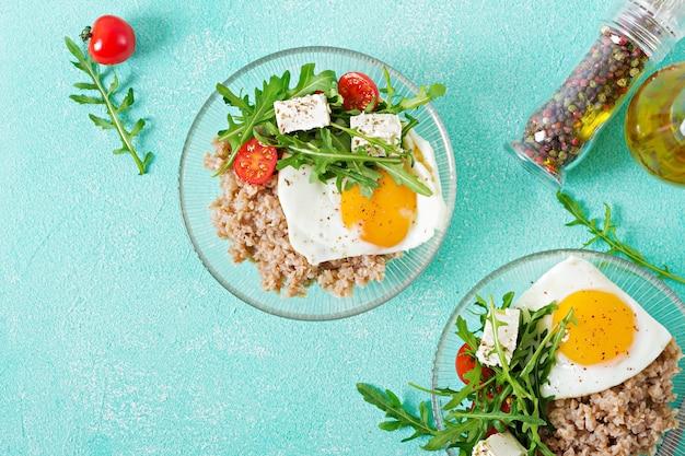 明るい背景に卵、フェタチーズ、ルッコラ、トマト、ソバのおridgeと健康的な朝食。適切な栄養。食事メニュー。平干し。上面図