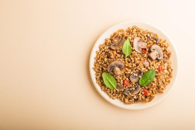 オレンジ色の背景にセラミックプレートにキノコと野菜のスペルト小麦(ディンケル小麦)おridge。平面図、コピースペース。