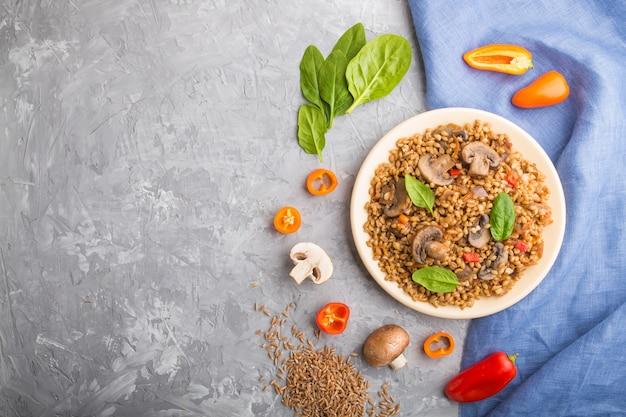 野菜と灰色のコンクリート背景にセラミックプレートにキノコのスペルト小麦(ディンケル小麦)おridge。トップビュー、フラットレイアウト、コピースペース。