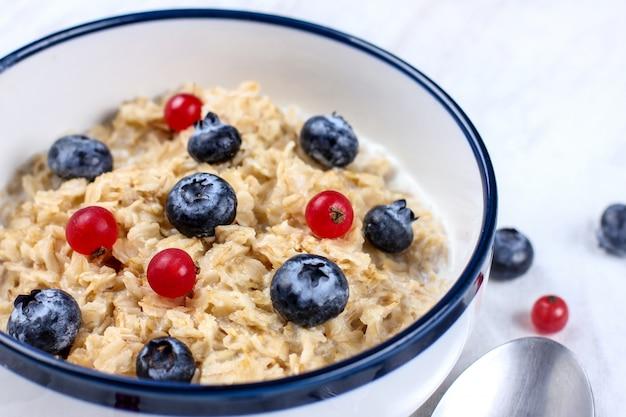 新鮮なブルーベリーと赤スグリの実のオートミール。ダイエット食品-スプーンで皿にオートミールのおridge。