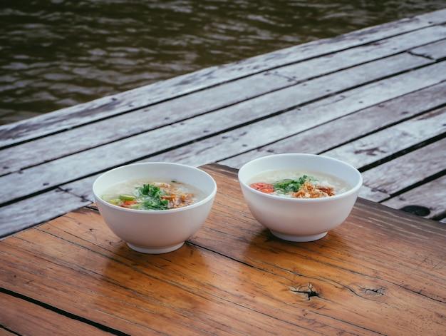 木製のテーブルに白いカップで豚肉のおridge