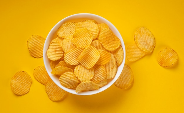 Ребристые картофельные чипсы в миске на желтом фоне с копией пространства