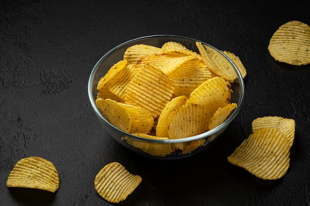 Ребристые картофельные чипсы на черном фоне
