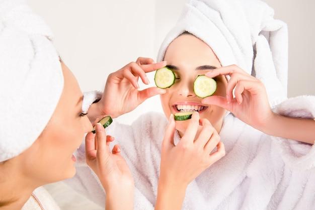 頭にタオルを持ったばかげた若い女性が、キュウリのスライスを他の人に食べさせます