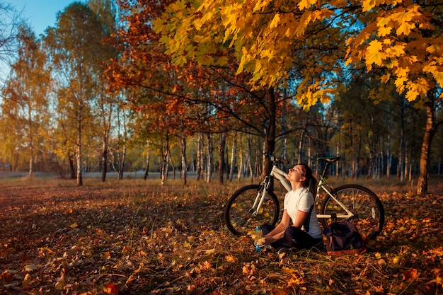 Riding bicycle in autumn forest, young woman biker relaxing after exercising on bike, healthy lifestyle