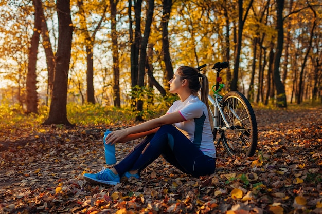 Riding bicycle in autumn forest, young woman having rest after workout on bike, healthy lifestyle