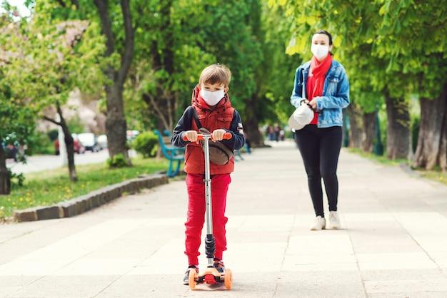 Езда мальчика на скутере в парке. мальчик носит медицинскую маску. мать и сын на прогулке
