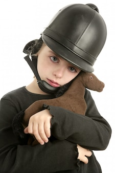 Riding cap little girl hug toy horse