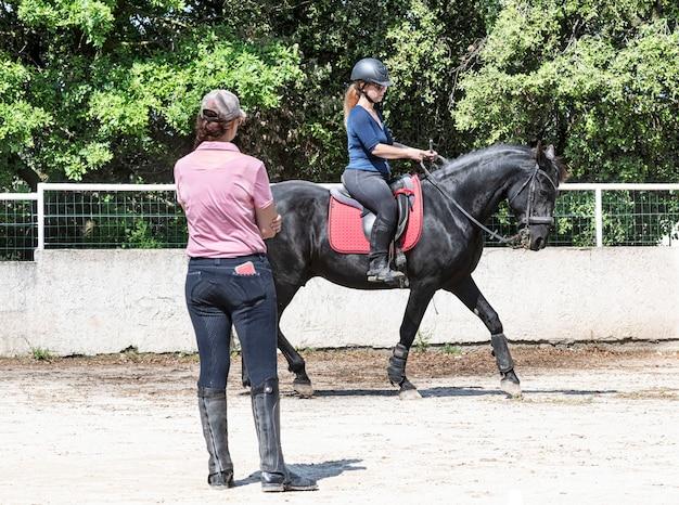 Девушка верхом и учитель тренируют ее вороного коня