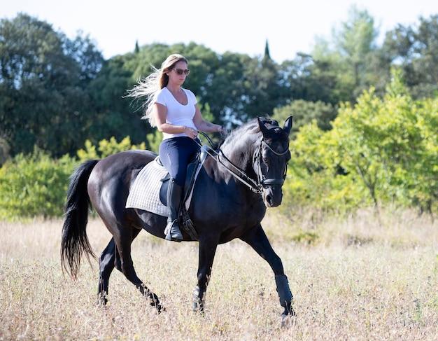 乗馬の女の子は彼女の黒い馬を訓練しています