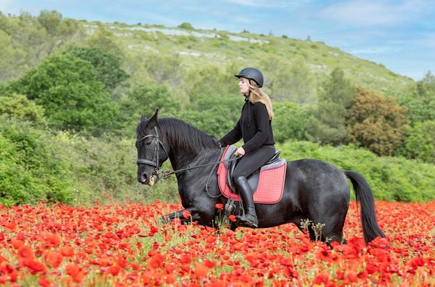 Девушка на лошади тренирует своего черного коня Premium Фотографии