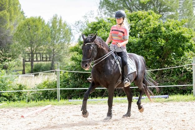 乗馬の女の子は馬術センターで彼女の馬を訓練しています