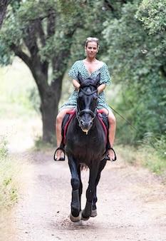 Езда девушка идет со своим черным конем