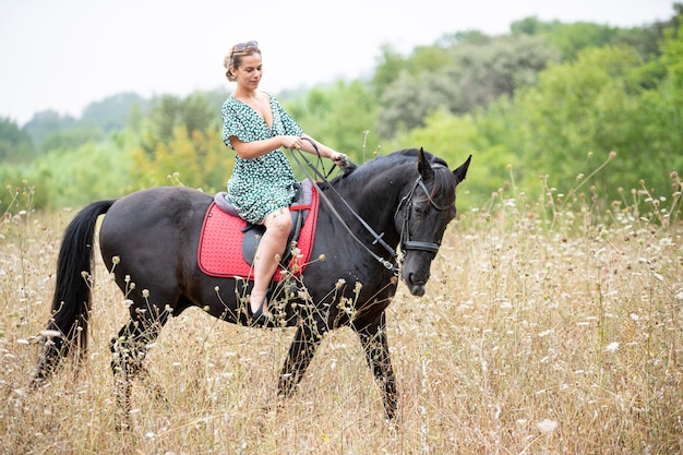 Riding girl are walking with her black horse