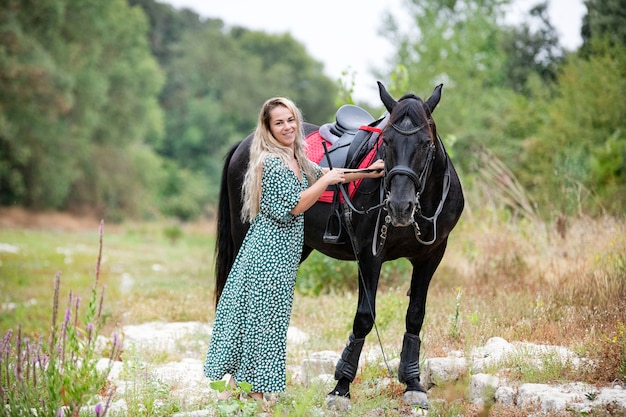 Верховая езда девушка идет со своим черным конем
