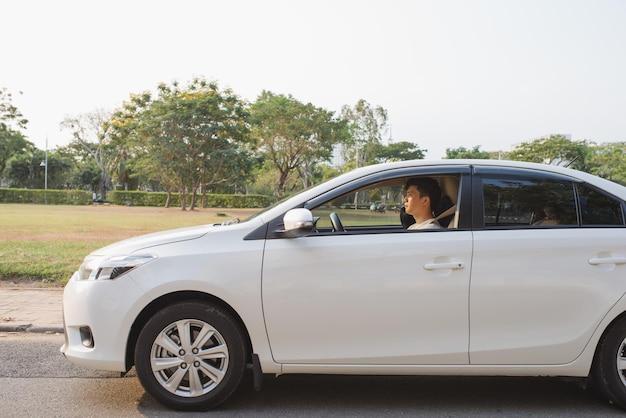 彼の新しい車に乗る。彼の車を運転し、笑顔のハンサムな若い男の側面図