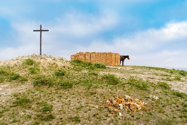러시아 andreevka orenburg 지역 마을 근처의 꼭대기 산에 있는 벽돌 더미 근처에서 말을 타고