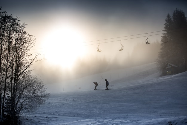 Riding skiers and ski lift against bright winter sun