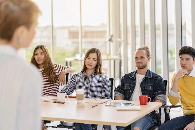 아시아 및 다민족 비즈니스 그룹에 대해 진지하게 이야기하는 관리자 여성의 rew 보기