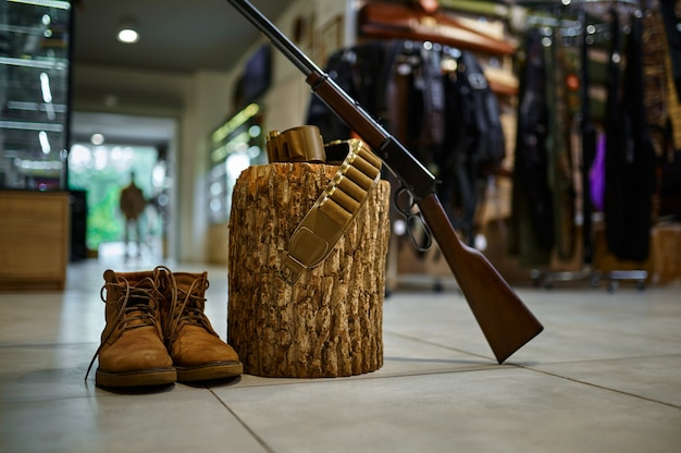 銃店の切り株にあるライフルとハンティングブーツ、誰も。背景の武器店のインテリア、弾薬の品揃え、銃器の選択、射撃の趣味とライフスタイル、自己防衛とセキュリティ