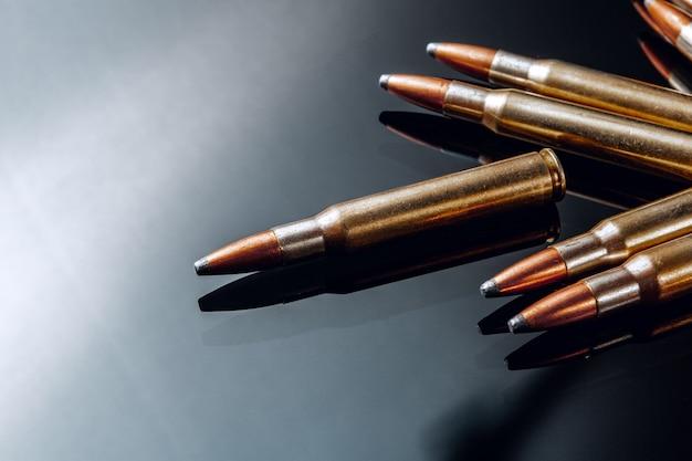黒の光沢のあるテーブル上のライフルの弾丸またはカートリッジ