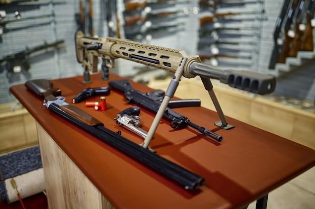 銃店のクローズアップのカウンターにあるライフルとピストル、誰も。背景の武器店のインテリア、弾薬の品揃え、銃器の選択、射撃の趣味とライフスタイル、自己防衛とセキュリティ