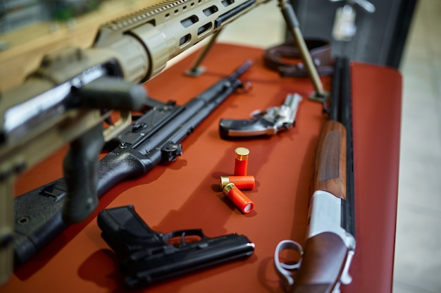 銃店のカウンターにあるライフルとピストル