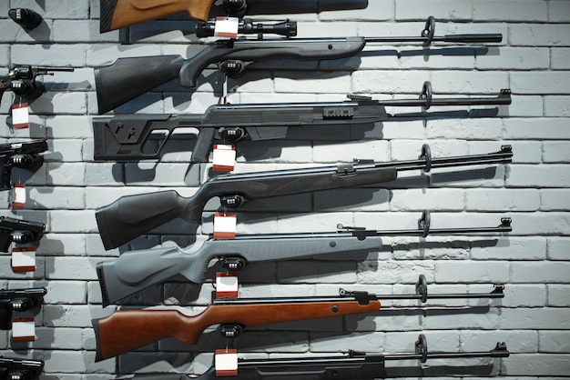 Rifles on showcase in gun shop closeup. equipment for hunters on stand in weapon store