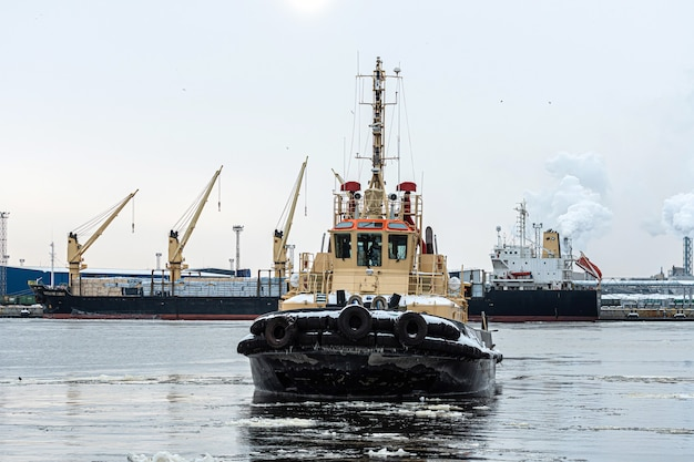 Riga, latvia - february 9, 2021: the tugboat returns to the cargo port on a cold and foggy winter morning