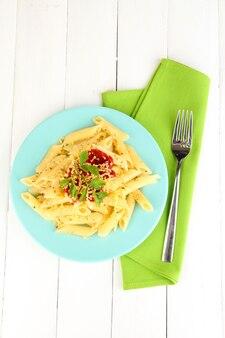 흰색 나무 테이블에 토마토 소스 리가 토니 파스타 접시