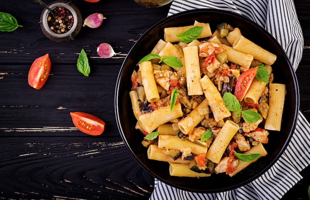 Rigatoni pasta with chicken meat, eggplant in tomato sauce in bowl. italian cuisine