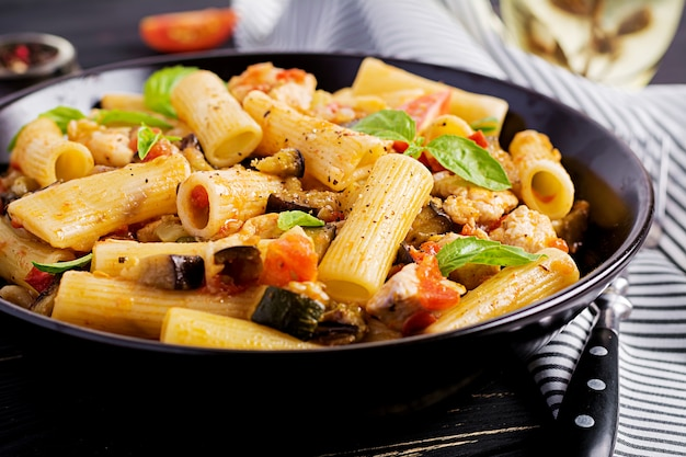 Rigatoni pasta with chicken meat and eggplant in tomato sauce in bowl