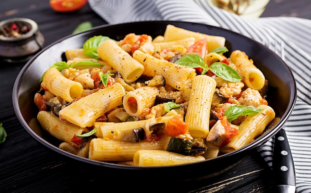 Rigatoni pasta with chicken meat, eggplant in tomato sauce in bowl.