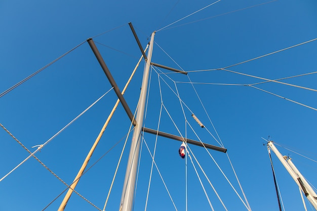 Rigging mast and halyards of a sailing boat under a beautiful blue sky