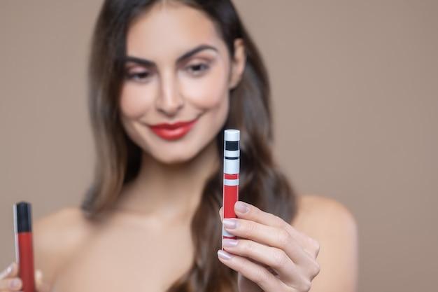 올바른 선택. 빨간색의 한 그늘을 선택하는 붉은 입술 광택을 보여주는 매니큐어와 여성 손