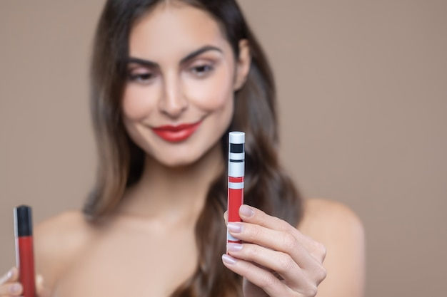 Right choice. female hand with manicure showing red lip gloss making selection of one shade of red