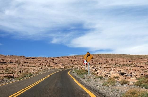 Правый поворот и указатель ограничения скорости на пустой дороге в пустыне атакама на севере чили